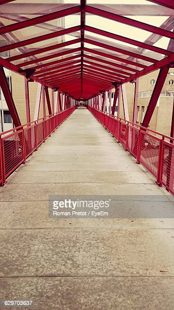 footbridge leading towards buildings - roman pretot stock-fotos und bilder
