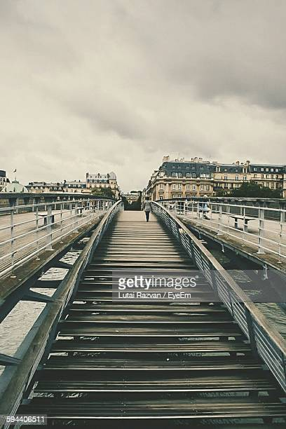 footbridge leading towards city against cloudy sky - lutai razvan stock pictures, royalty-free photos & images
