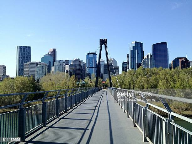 Footbridge Leading Towards City Buildings Against Clear Sky