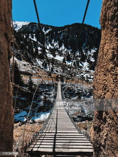 footbridge leading towards mountain against clear sky during winter - andorra stock pictures, royalty-free photos & images