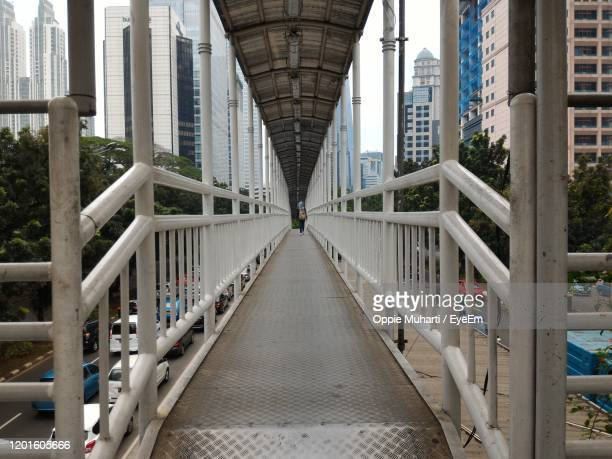 footbridge over footpath amidst buildings in city - oppie muharti stock pictures, royalty-free photos & images