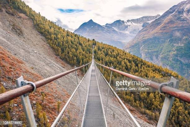 footbridge over mountain against sky - valais canton stock pictures, royalty-free photos & images