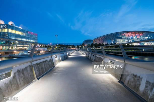 footbridge over river leading to illuminated city, glasgow, scotland, uk - image stock pictures, royalty-free photos & images