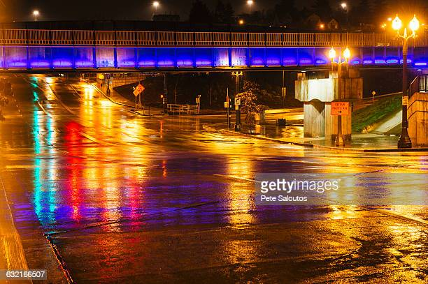 Footbridge over wet city road at night, Tacoma, Washington, USA