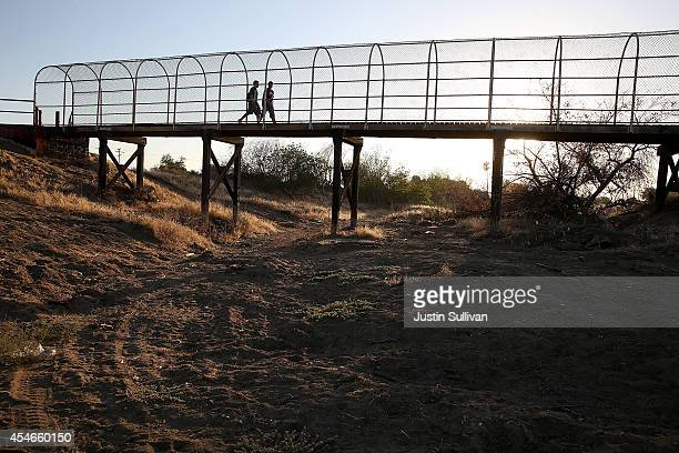 A footbridge spans a completely dry river bed on September 4 2014 in Porterville California Over 300 homes in the California central valley city of...