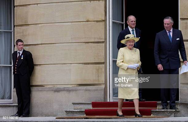 Footman Wearing His Medal To Mark The Golden Jubilee Watches As Queen Elizabeth II Walks Out Of Buckingham Palace Into Her Garden For A Children's...