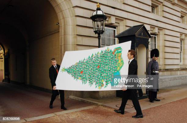 Footmen carry a giant Christmas card for Queen Elizabeth II which was delivered Thursday December 15 to Buckingham Palace in London. The card bears...