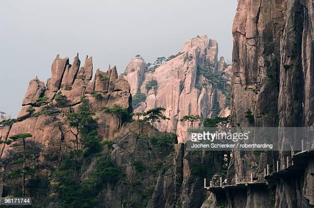 footpath along rock face, xihai (west sea) valley, mount huangshan (yellow mountain), unesco world heritage site, anhui province, china, asia - unesco stockfoto's en -beelden