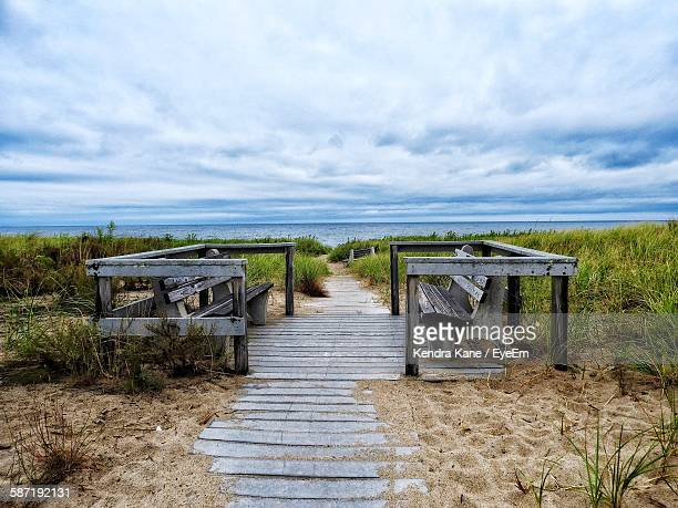 Footpath Amidst Benches Leading Towards Sea Against Cloudy Sky