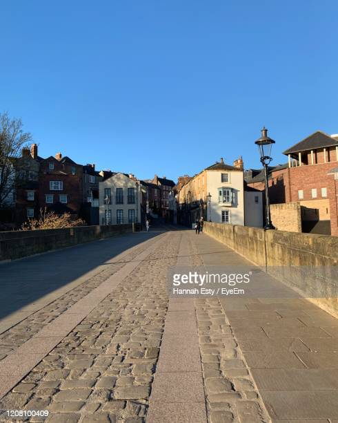 footpath amidst buildings against blue sky - alley stock pictures, royalty-free photos & images