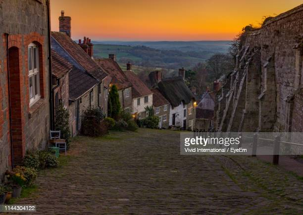footpath amidst buildings against sky at sunset - village stock pictures, royalty-free photos & images