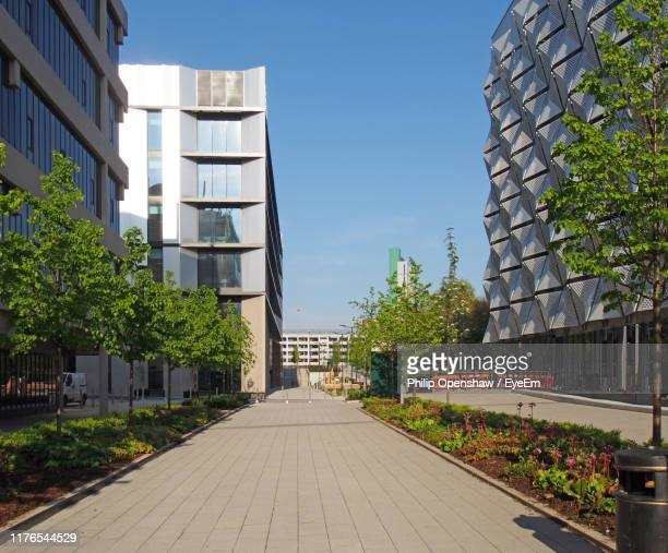 footpath amidst buildings against sky in city - campus stock pictures, royalty-free photos & images