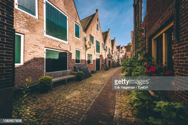 footpath amidst buildings in town - middelburg netherlands stock pictures, royalty-free photos & images