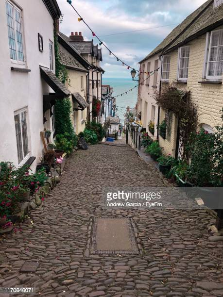 footpath amidst buildings in town - devon stock pictures, royalty-free photos & images