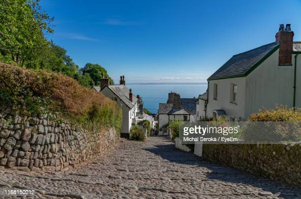 footpath amidst houses and buildings against blue sky - devon stock pictures, royalty-free photos & images