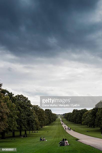 footpath amidst trees at windsor castle against cloudy sky - windsor castle stock pictures, royalty-free photos & images