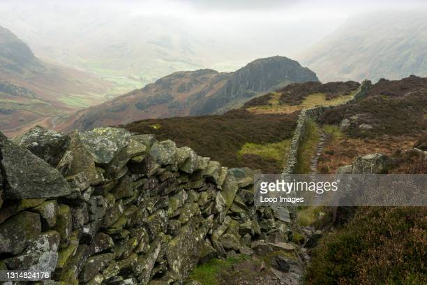 Footpath and dry stone wall on Lingmoor Fell with Side Pike beyond in the English Lake District National Park.