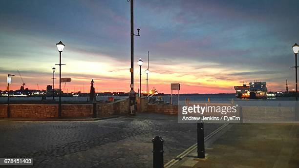 footpath and sea against sky during sunset - bollard stock photos and pictures