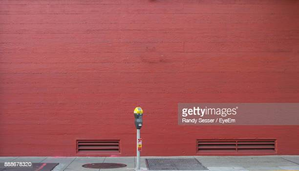 footpath by red brick wall - parking meter stock photos and pictures