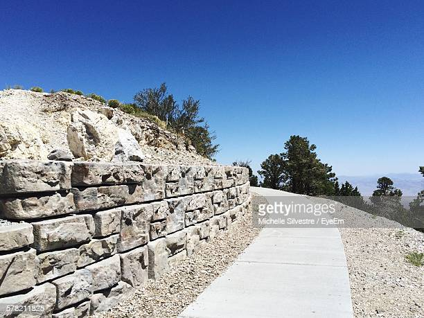 footpath by stone retaining wall against clear blue sky at mount charleston - mt charleston stock photos and pictures