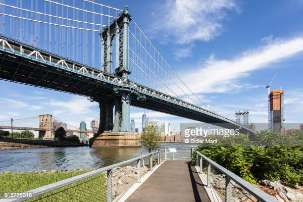 footpath in park under the manhattan bridge in the dumbo area of brooklyn with manhattan in the background in new york - dumbo stock photos and pictures
