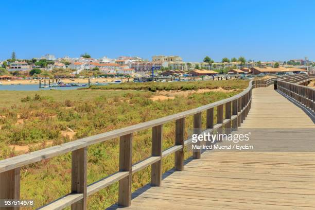 footpath in town against clear blue sky - alvor stock pictures, royalty-free photos & images