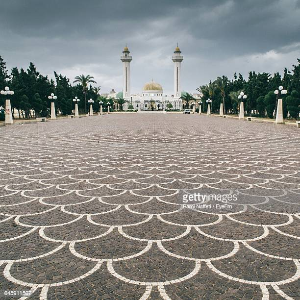 footpath leading towards bourguiba mosque against cloudy sky - sousse stock pictures, royalty-free photos & images