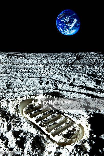 A footprint on the surface of the moon and Planet Earth in the background