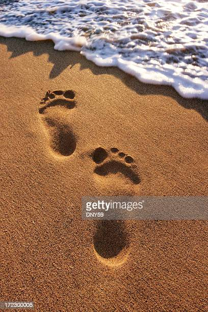 Footprints about to be washed away by the surf