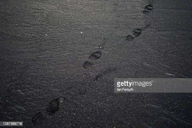 Footprints are left in sea coal deposited on Saltburn beach on November 24 2020 in Saltburn By The Sea England Sea coal washes up onto beaches either...