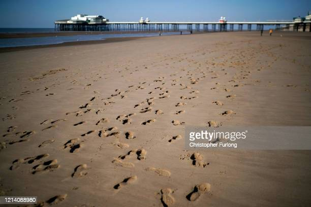 Footprints are left in the sand as people keep their social distance on a near deserted Blackpool beach on March 22, 2020 in Blackpool, England. Many...