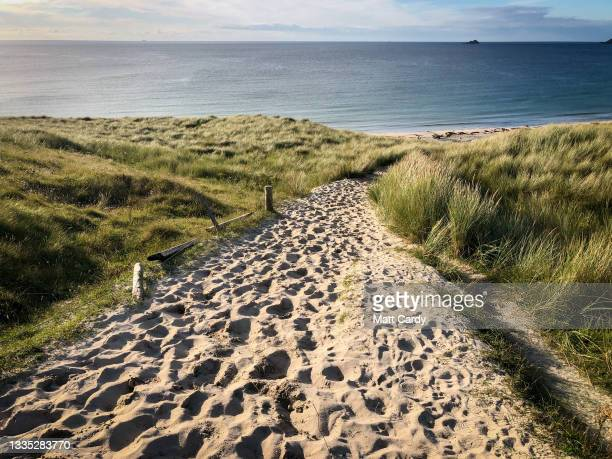 Footprints are left in the sand on a path leading to Sennen Cove on August 13, 2021 near Penzance in Cornwall, England. The ongoing international...