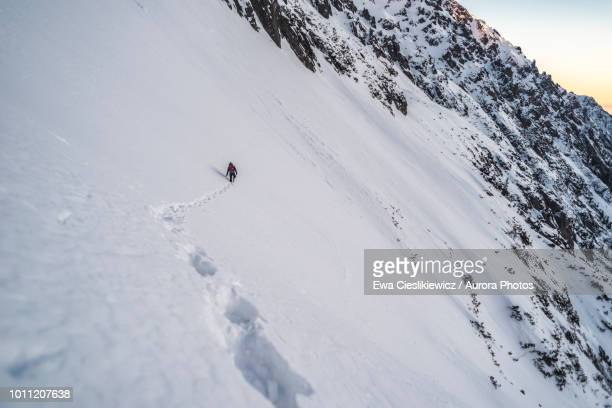 Footprints in snow and mountain climber in distance, Tatra Mountains, Malopolskie Province, Poland