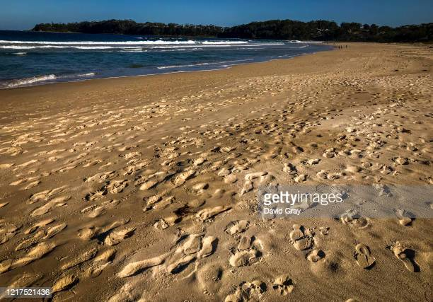 Footprints in the sand left by people walking Narrawallee Beach can be seen on March 27, 2020 in Mollymook, Australia. Public gatherings are now...