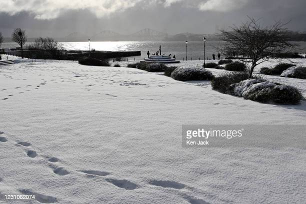 Footprints in the snow near the Fife Coastal Path with the Forth Bridge in the background, as many parts of Scotland experience significant...