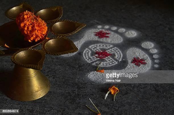 Footprints of Goddess Lakshmi-Rangoli-with marigold flower and brass lamp/Diwali