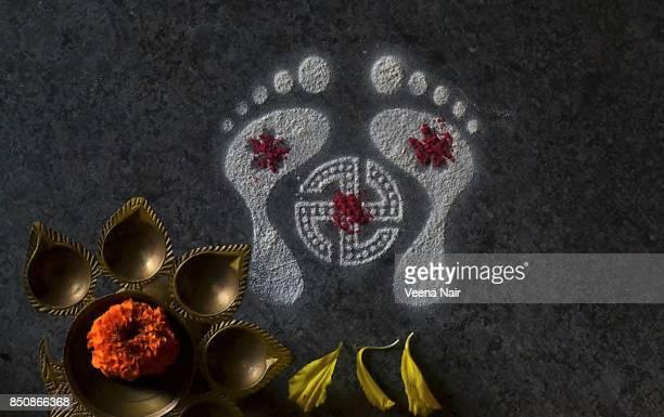 footprints of goddess lakshmi-rangoli-with marigold flower and brass lamp/diwali - goddess lakshmi stock photos and pictures
