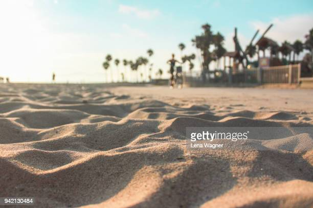 footsteps in sand against palm tree beach scene - la beach stock pictures, royalty-free photos & images