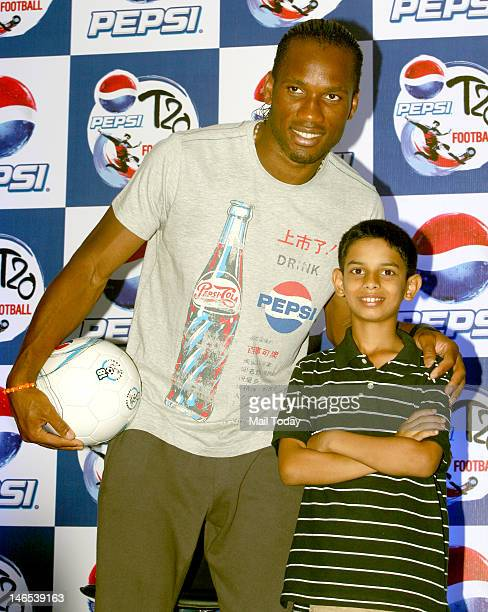 Foottballer Didier Drogba pose with a child at a news conference in Thyagaraj Stadium in New Delhi on Sunday 17th June 2012