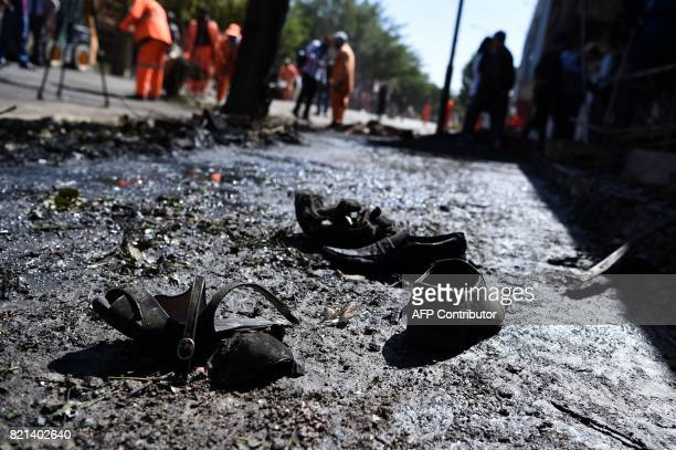 TOPSHOT Footwear of victims are seen on the ground as Afghan residents inspect the site of a car bomb attack in western Kabul on July 24 2017 At...
