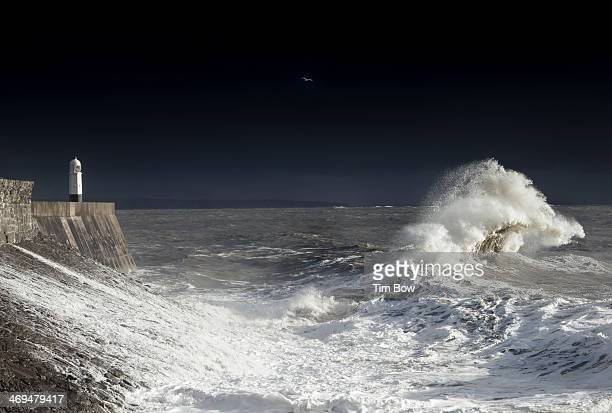 For a brief moment the sun comes out inbetween weather fronts as two large waves crash into each other in Porthcawl, UK in the wildest winter weather...