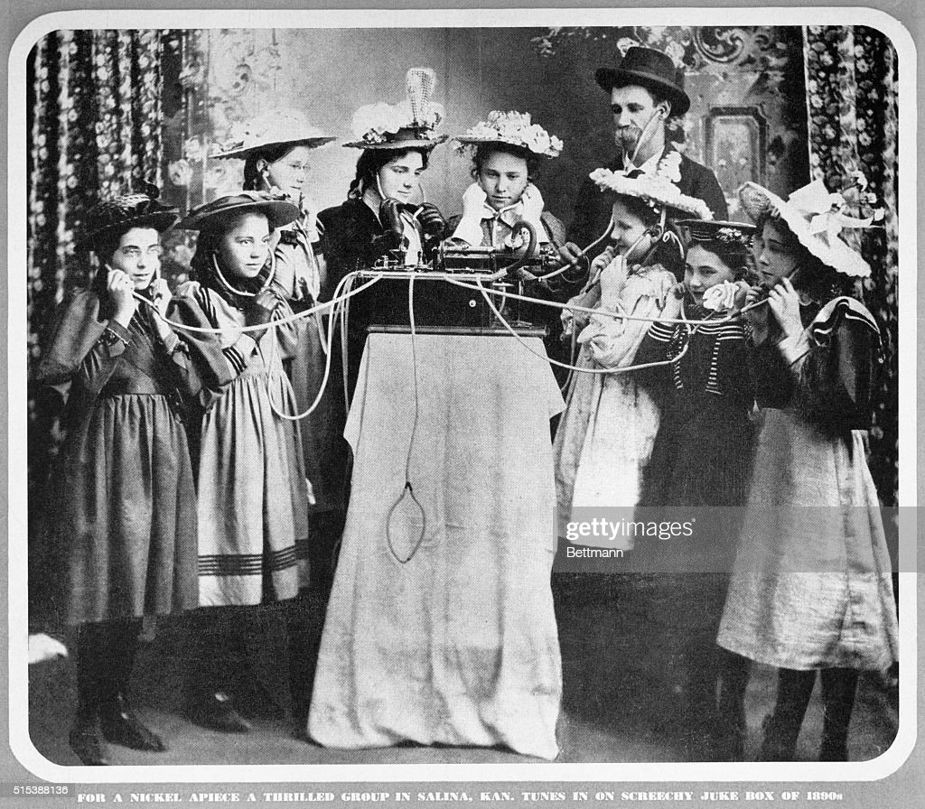 For a nickel apiece a thrilled group in Salina, Kansas tunes in on a screechy juke box of 1890s.