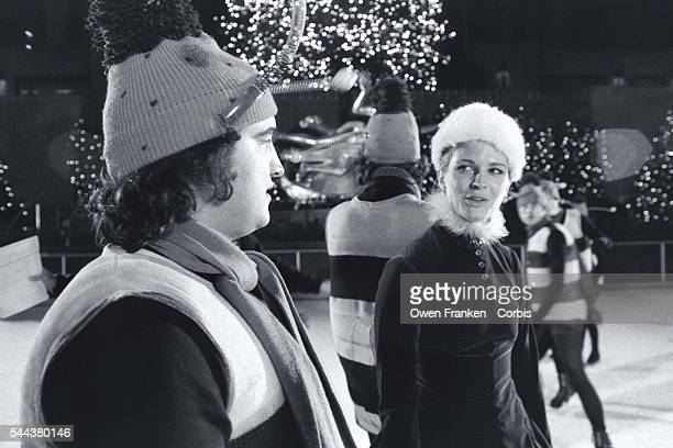 For a Saturday Night Live skit comedian John Belushi wears a bumble bee costume and actress Candice Bergen wears a Santa's helper costume