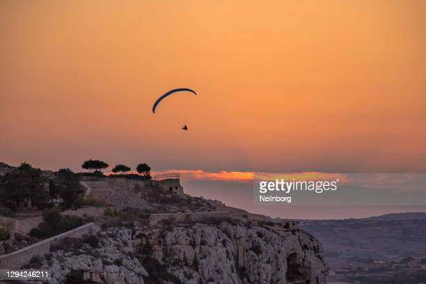 lone para glider flying during sunset