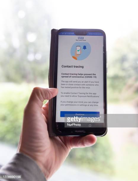 For illustrative purposes a woman holds a mobile phone with Covid-19 tracking and tracing app opened while NHS launches new application in England...