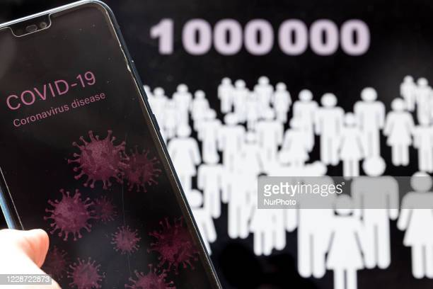 For illustrative purposes a woman holds a mobile phone with Covid-19 graphics against one million people graphics the death toll of Covid 19 deaths...