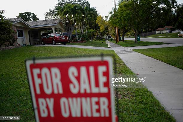 A 'For Sale By Owner' sign stands in front of a house in Miami Florida US on Monday June 15 2015 The National Association of Realtors is scheduled to...