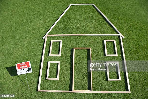For sale' sign and house outline in grass