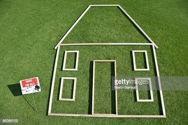Für sale'Zeichen und Haus Kontur in grass
