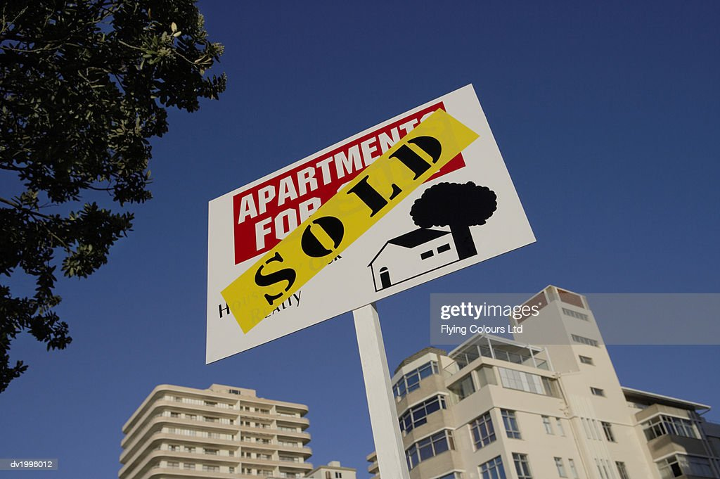 For Sale Sign in Front of a Block of Apartments : Stock Photo